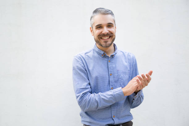 Smiling young man applauding Smiling young man applauding. Handsome stylish guy clapping hands and looking at camera. Applause concept medium shot stock pictures, royalty-free photos & images