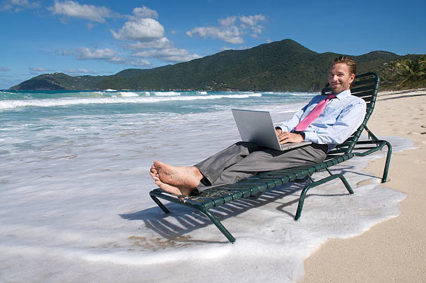 Smiling Young Man Businessman Relaxing on Beach Chair with Laptop stock photo
