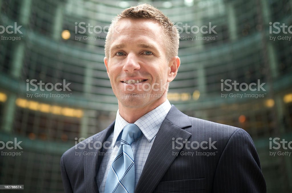 Smiling Young Man Businessman Standing Outdoors in Office Courtyard stock photo