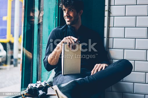 1174436608 istock photo Smiling young man dressed in black shirt looking out of window holding notepad with mock up area for advertising.Cheerful hipster guy with notebook sitting in coworking space during free time 1168817224