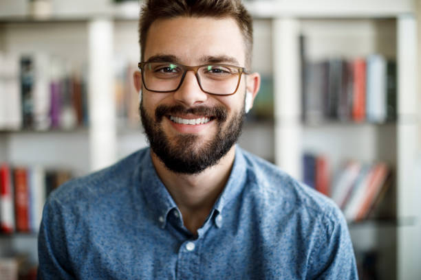 Smiling young man having online conference from home office stock photo