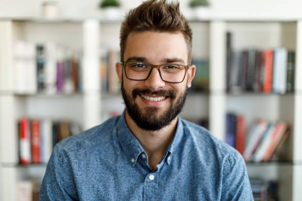 Smiling young man having online conference from home stock photo