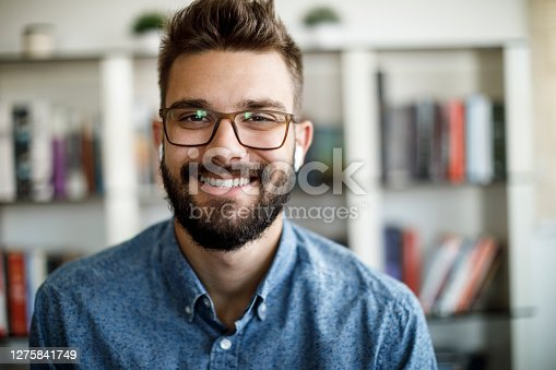 Smiling young man having online conference from home