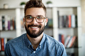 istock Smiling young man having online conference from home 1275841749