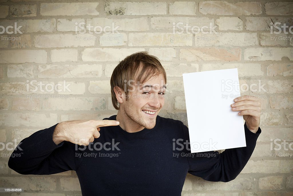 Smiling Young Man Holding and Pointing a Blank Paper royalty-free stock photo