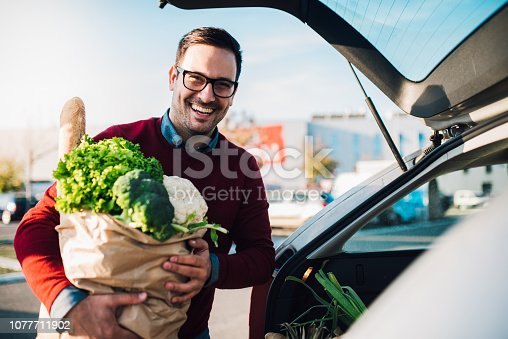 Happy young man holding a bag full of groceries