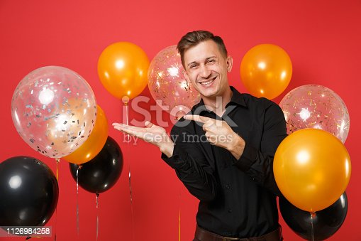 istock Smiling young man in black classic shirt pointing hand, index finger aside on red background air balloons. Valentine's, International Women's Day, Happy New Year birthday mockup holiday party concept. 1126984258