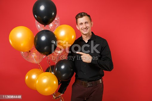 istock Smiling young man in black classic shirt pointing index finger on air balloons in hand isolated on bright red background. St. Valentine's Day, Happy New Year, birthday mockup holiday party concept. 1126984448