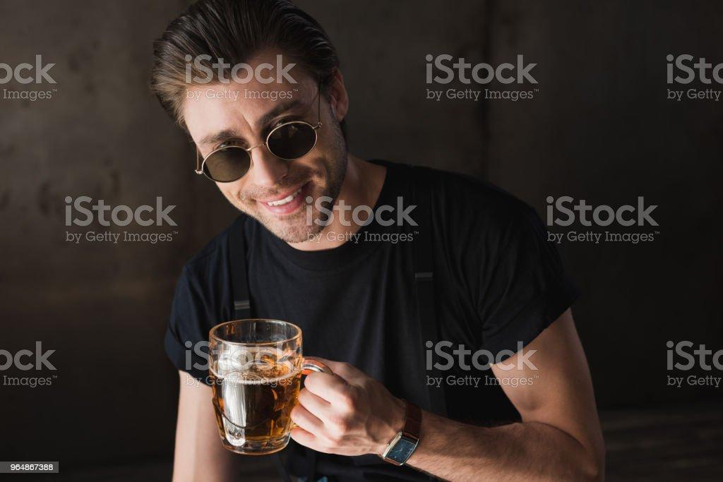 jovem em t-shirt preta e óculos escuros, segurando a caneca de cerveja e olhando para a câmera a sorrir - Foto de stock de Acessório royalty-free