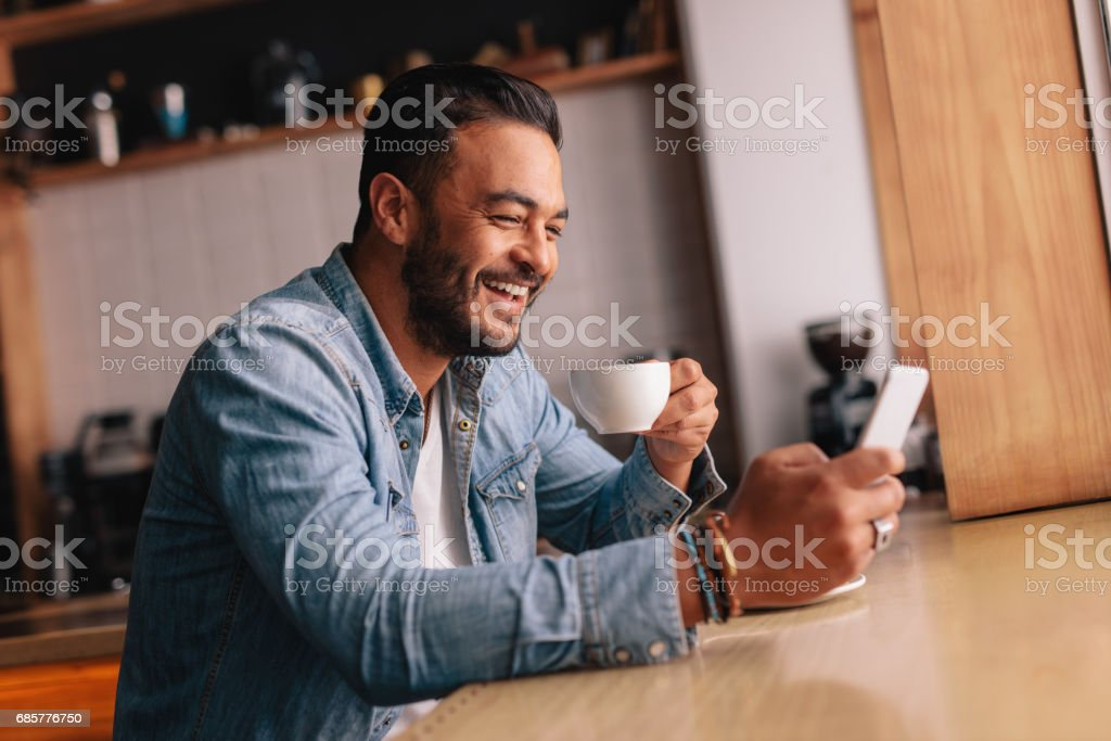 Smiling young man in cafe using mobile phone royalty-free stock photo