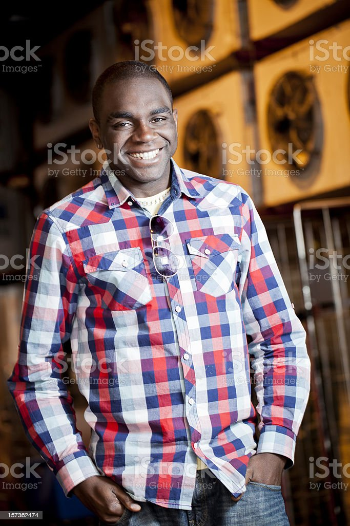 Smiling Young man in industrial setting stock photo