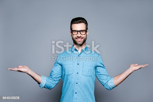 istock Smiling young man in jeans shirt showing a balance of two products isolated on gray background 944043528