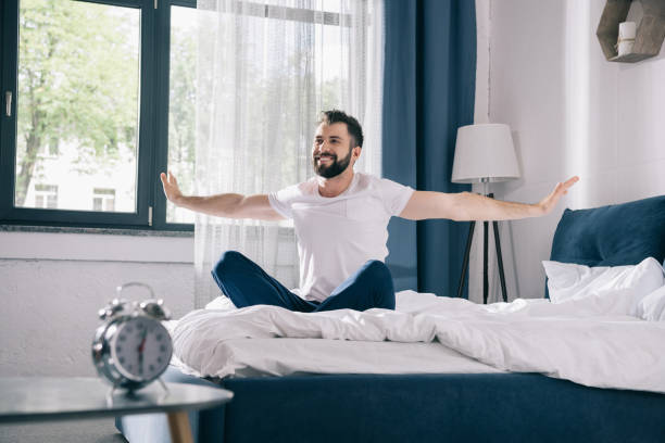 Smiling young man in pajamas stretching while sitting on bed at morning stock photo