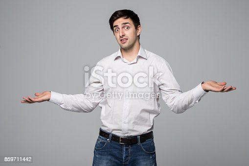 istock Smiling young man in shirt showing a balance of two products isolated on gray background. 859711442