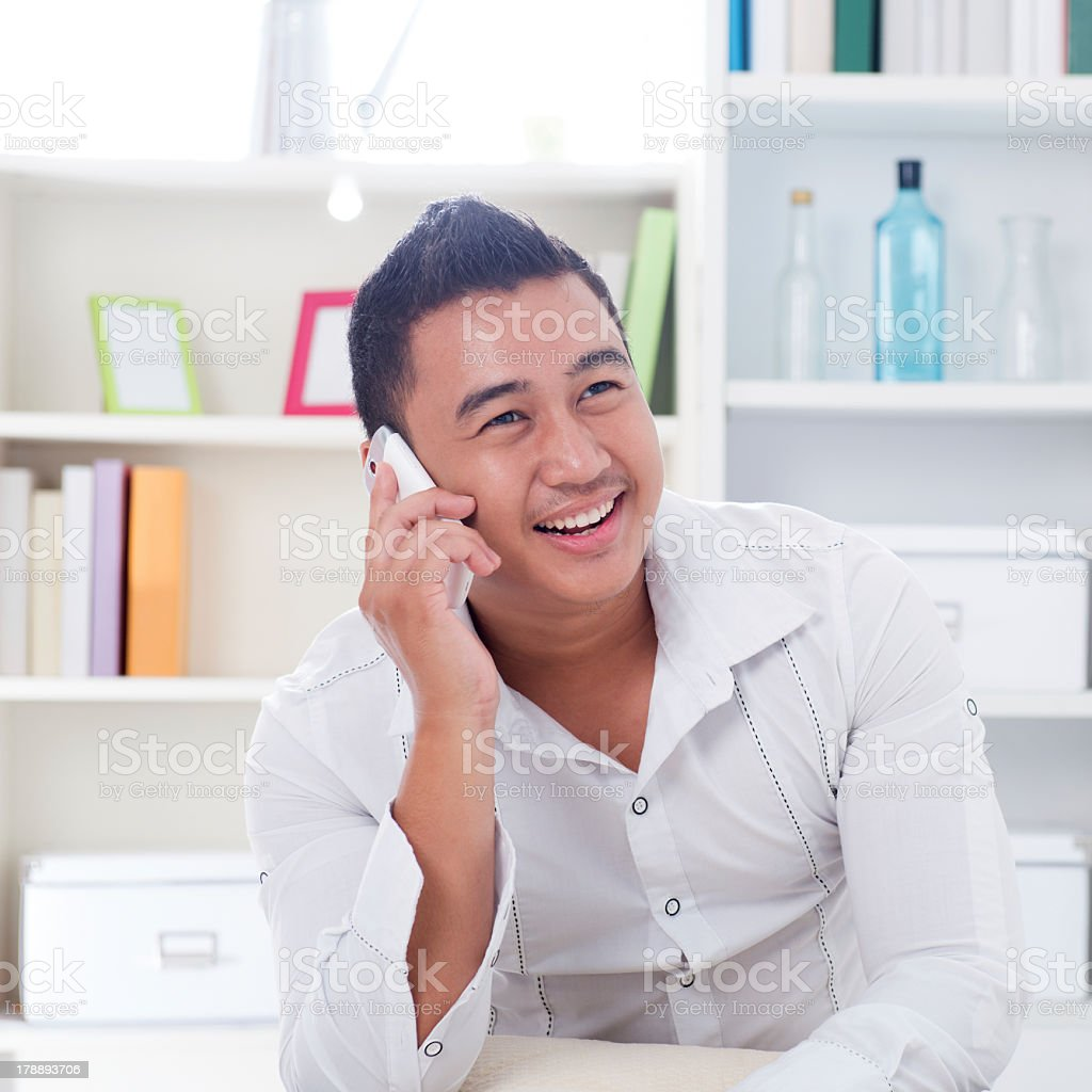 Smiling young man in white shirt taking on a phone stock photo