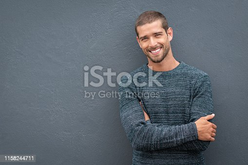 Portrait of happy young man leaning against wall isolated on grey background with a big smile. Handsome cheerful guy in winter clothes on gray wall looking at camera. Stylish man wearing sweater with crossed arms standing against wall with copy space.