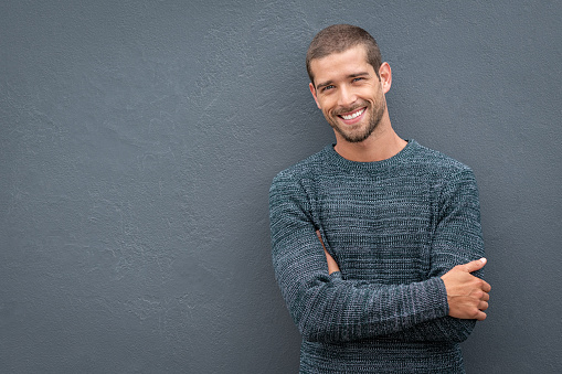 istock Smiling young man leaning against grey wall 1158244711