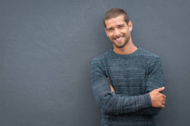Smiling young man leaning against grey wall Portrait of happy young man leaning against wall isolated on grey background with a big smile. Handsome cheerful guy in winter clothes on gray wall looking at camera. Stylish man wearing sweater with crossed arms standing against wall with copy space. charming stock pictures, royalty-free photos & images