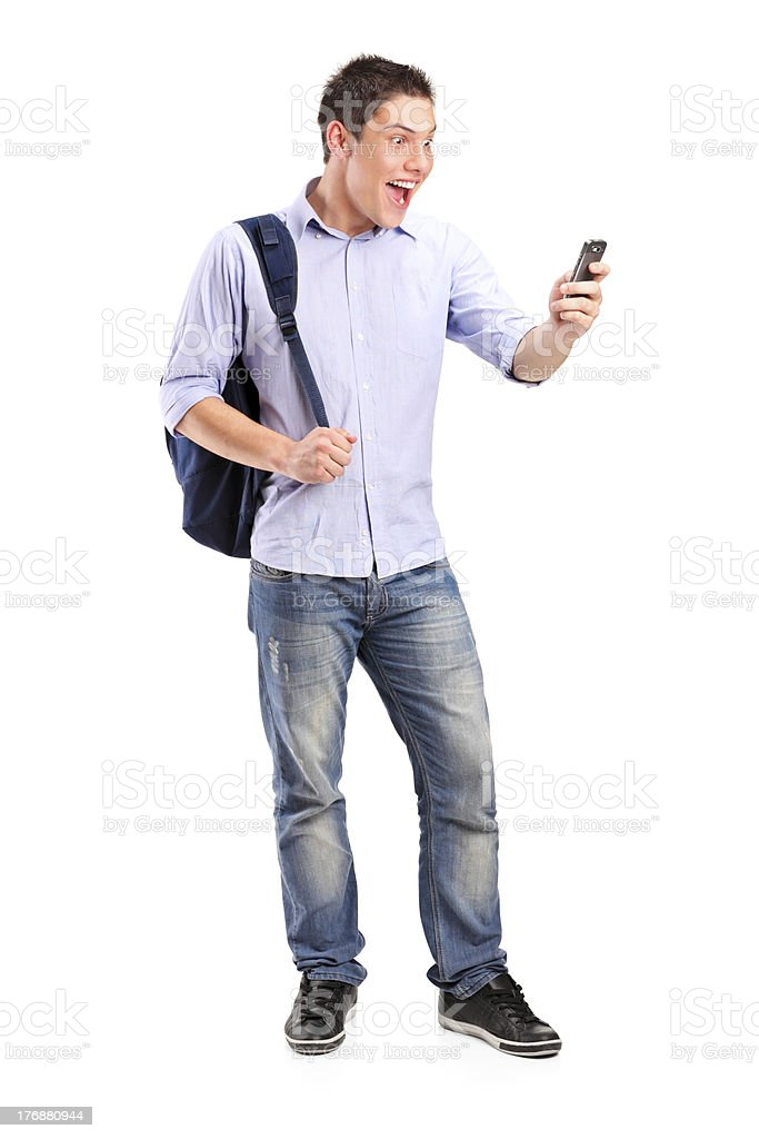 Smiling young man looking at a cell phone royalty-free stock photo