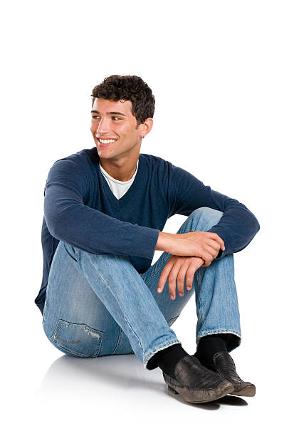 smiling young man, looking away from the camera - sitting on floor stock photos and pictures
