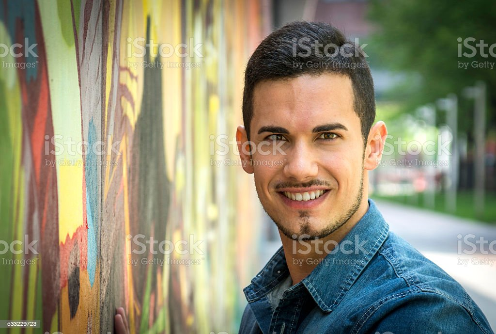 Smiling young man next to colorful graffiti wall stock photo
