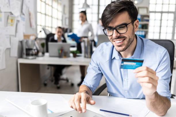 lächelnd jungen mann bezahlen mit kreditkarte im büro - brille bestellen stock-fotos und bilder
