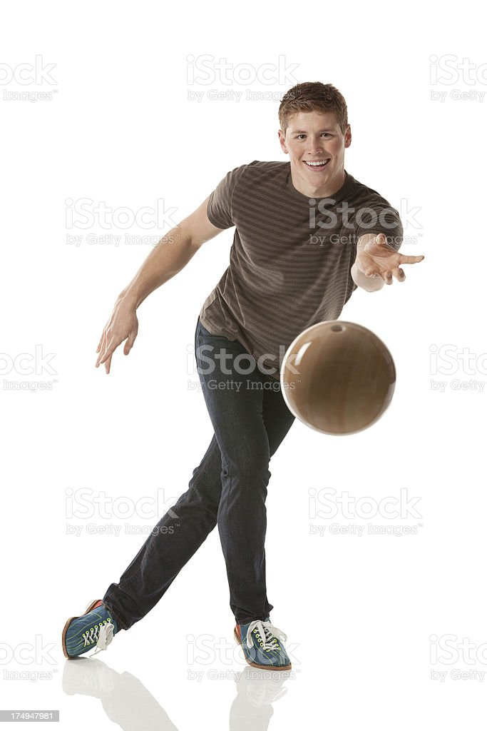 Smiling young man playing with a bowling ball royalty-free stock photo