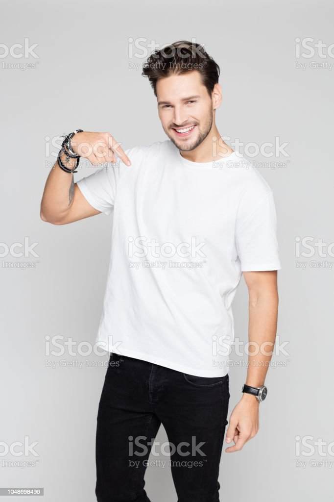 Smiling young man pointing down Portrait of happy young man pointing down and smiling on grey background 25-29 Years Stock Photo