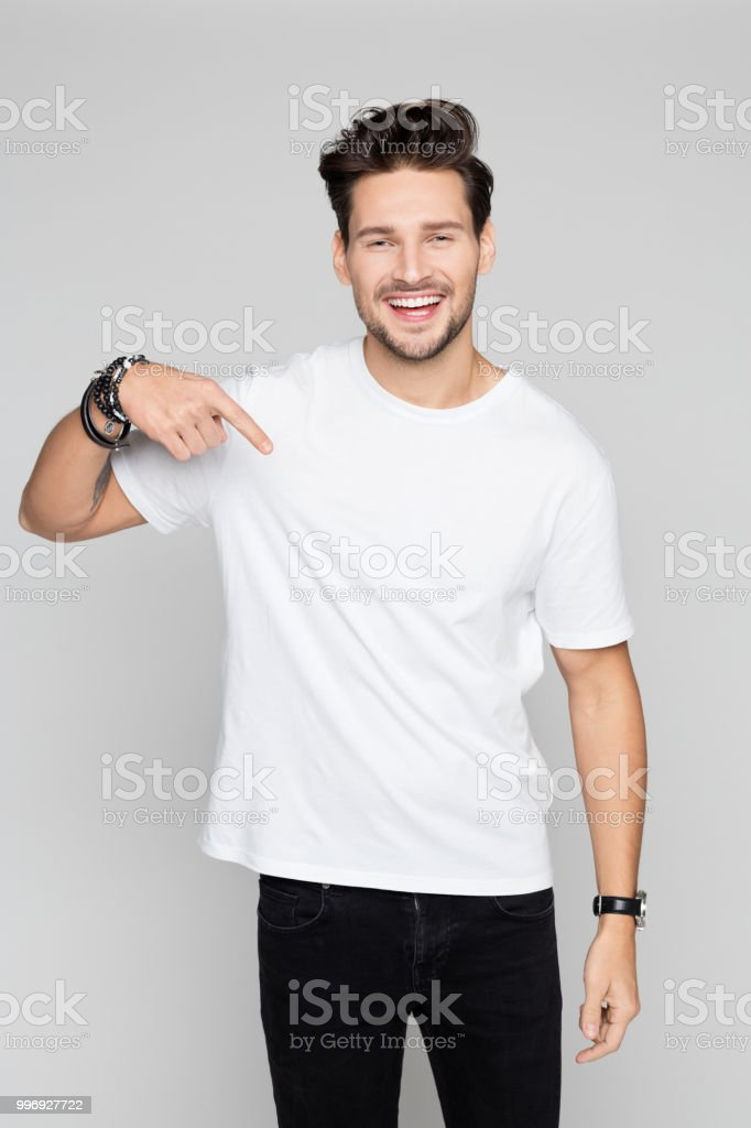Smiling young man pointing down Portrait of young man pointing down and smiling on grey background 25-29 Years Stock Photo