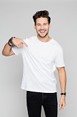 istock Smiling young man pointing down 996927722