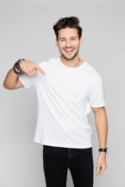 smiling young man pointing down - t shirt stock photos and pictures