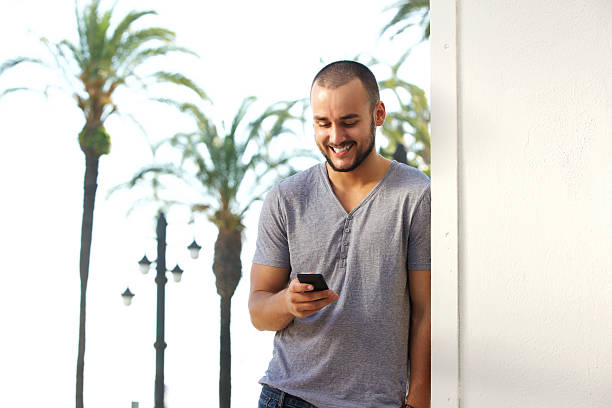 Smiling young man reading text message on mobile phone Portrait of a smiling young man reading text message on mobile phone shaved head stock pictures, royalty-free photos & images