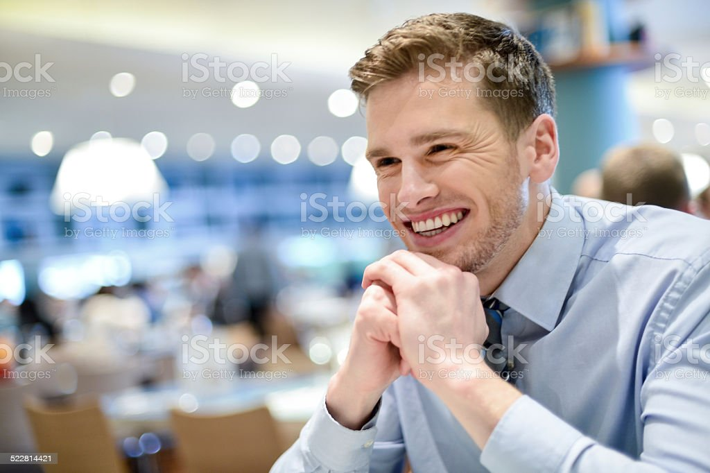 Smiling young man relaxing in a cafe stock photo