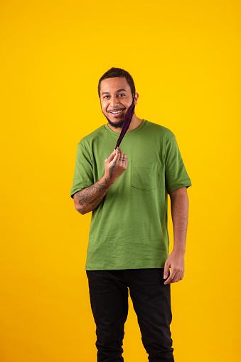 Smiling young man removing protective face mask against orange background