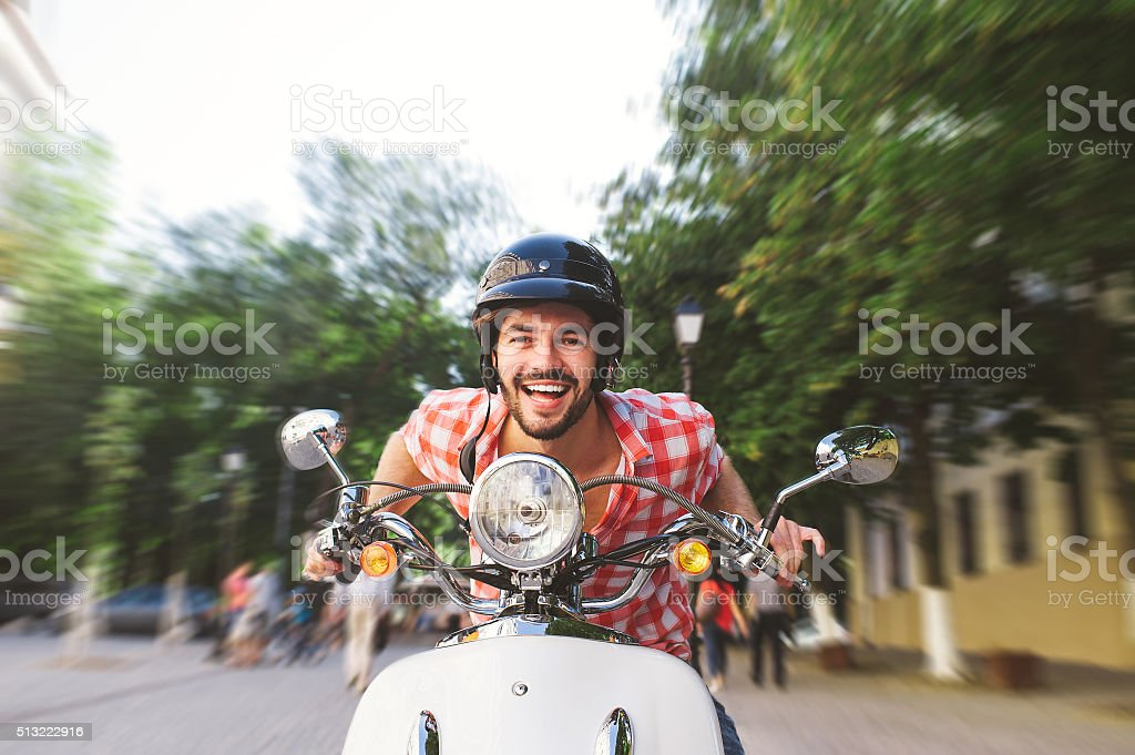 Smiling Young Man Riding Motor Scooter stock photo