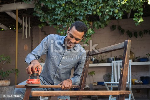 Smiling young man sanding a chair outdoors