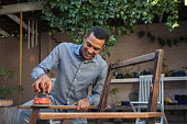 istock Smiling young man sanding a chair outdoors 1014097602