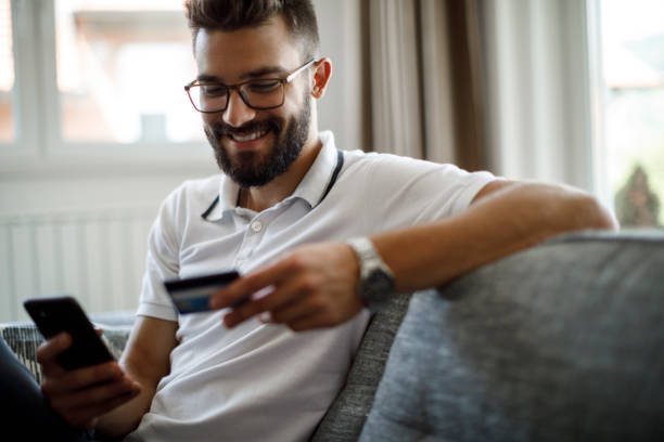 Smiling young man shopping online stock photo