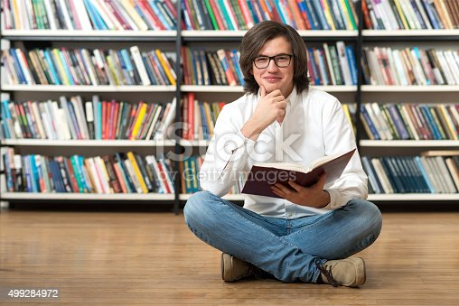 500129038istockphoto smiling young man sitting on the floor with crossed leg 499284972