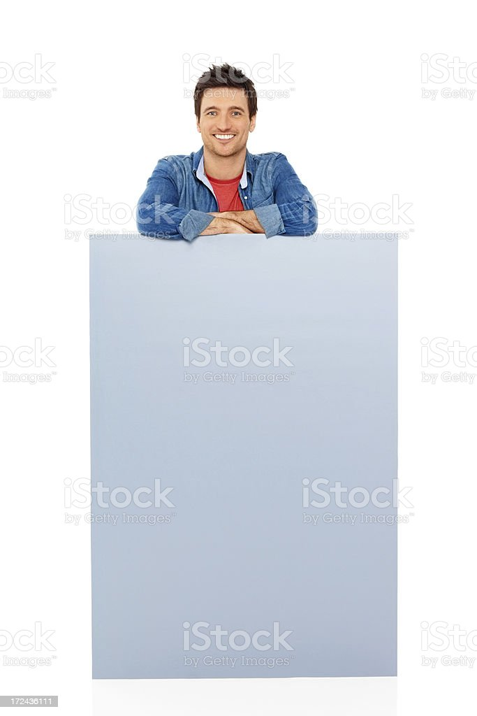 Smiling young man standing behind blank billboard over white royalty-free stock photo