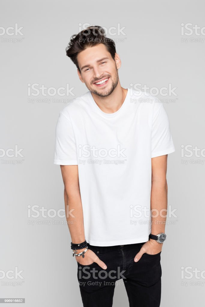Smiling young man standing relaxed Portrait of attractive young man with hands in pocket smiling on grey background 25-29 Years Stock Photo