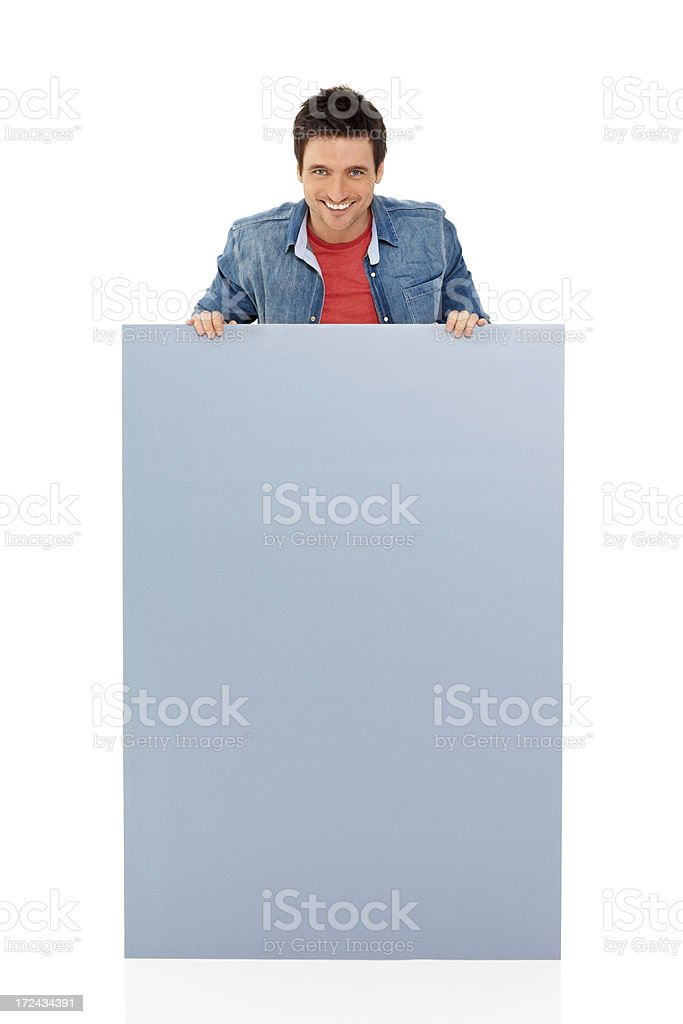 Smiling young man standing with a blank billboard in front royalty-free stock photo