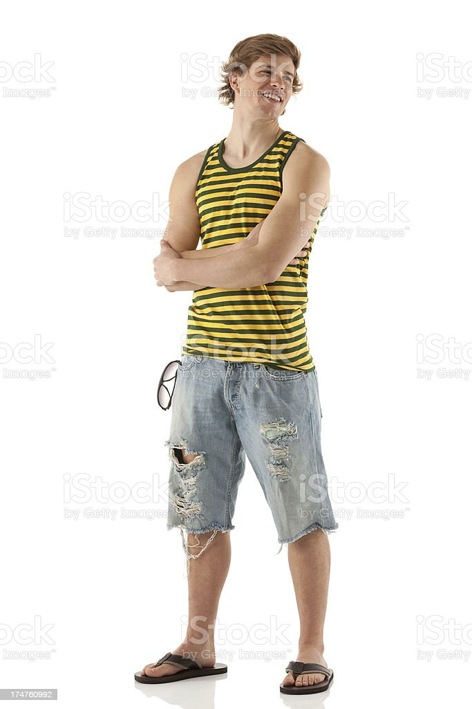 Smiling young man standing with his arms crossed stock photo