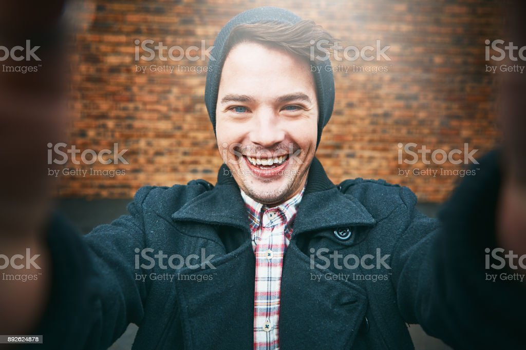 Smiling young man taking selfie by brick wall stock photo