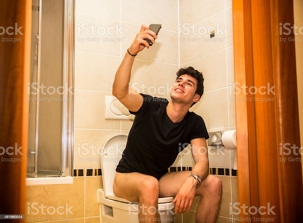 Smiling young man taking selfie while defecating stock photo