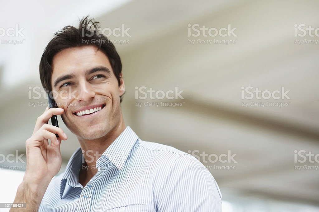 Smiling young man talking on cellphone royalty-free stock photo