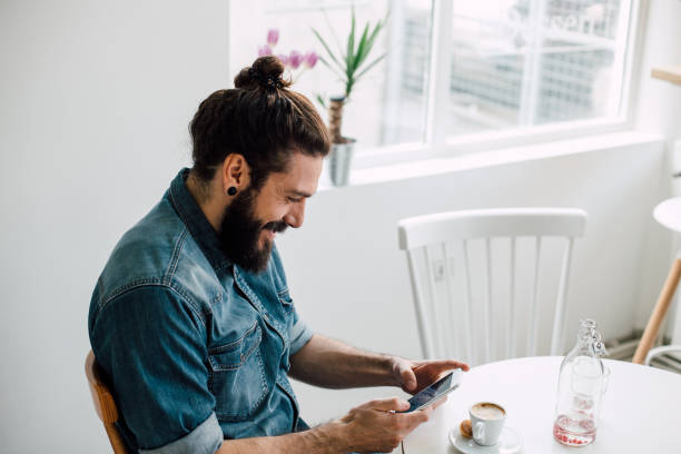 Smiling young man typing on his phone at a coffee shop Happy young man typing on his mobile phone screen at a coffee shop man bun stock pictures, royalty-free photos & images