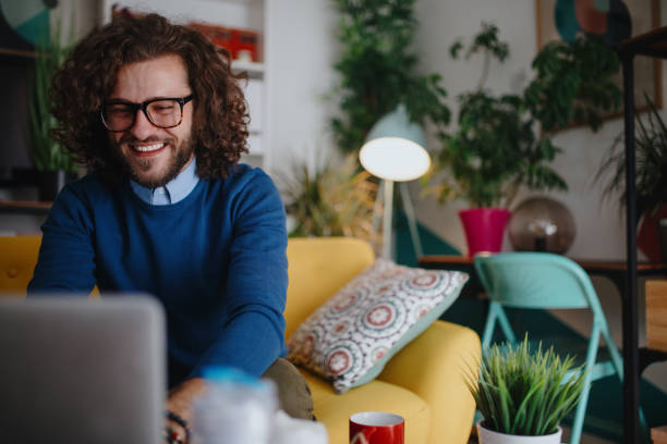 Smiling young man using laptop at home stock photo