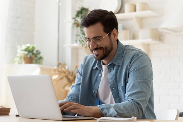 Smiling young man using laptop studying working online at home stock photo