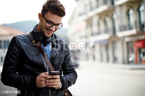 Smiling young man using mobile phone outdoor